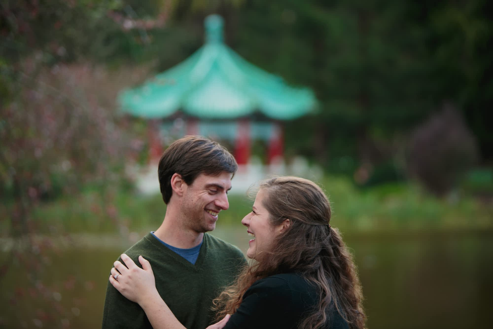 The engaged couple are laughing with each other in front of the Chinese Pavilion at Stow Lake.