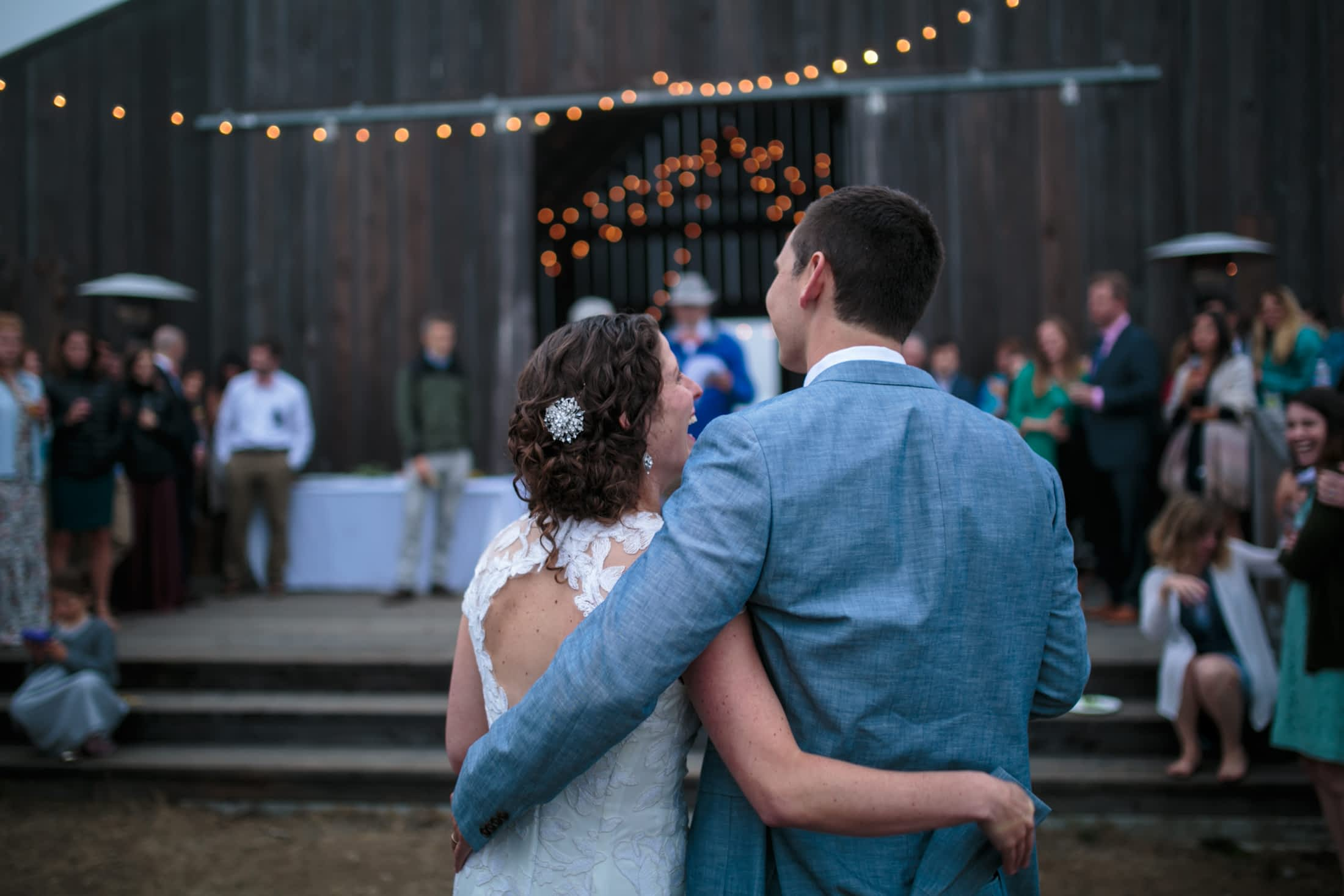 The barn at Cuffey's Cove is lit up with Christmas lights, inside and out. The bride and groom stand outside laughing with their arms around each other.