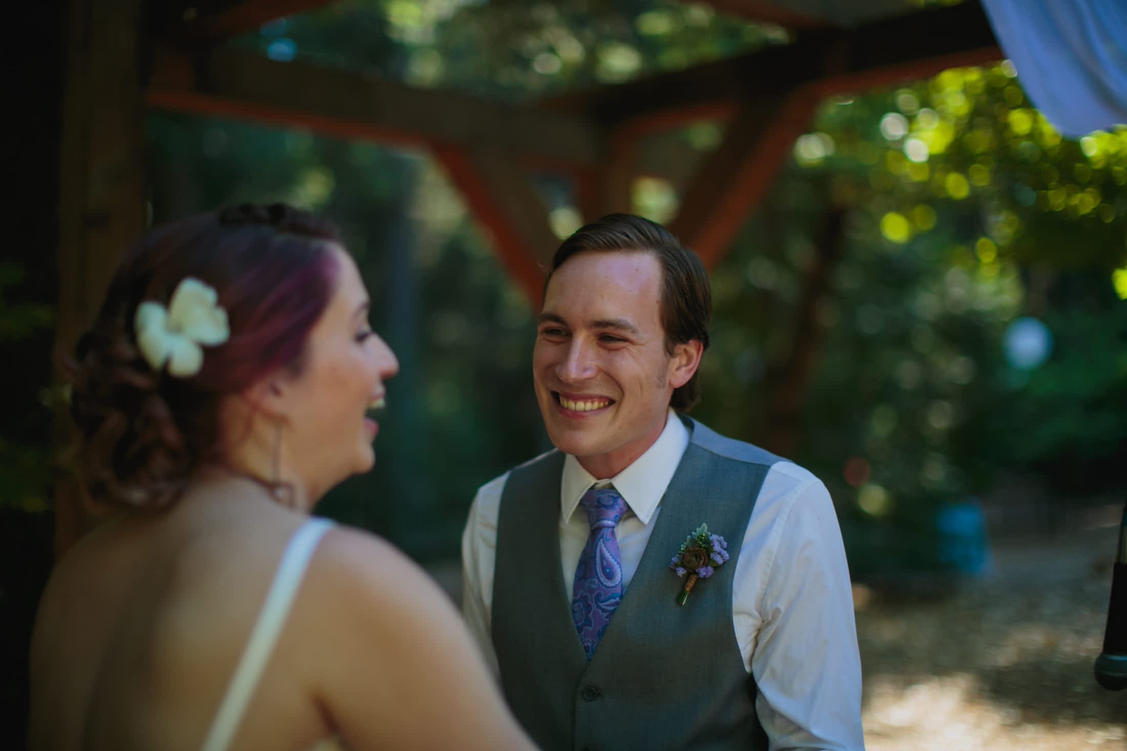 The groom is smiling at his bride while she laughs looking at their guests.