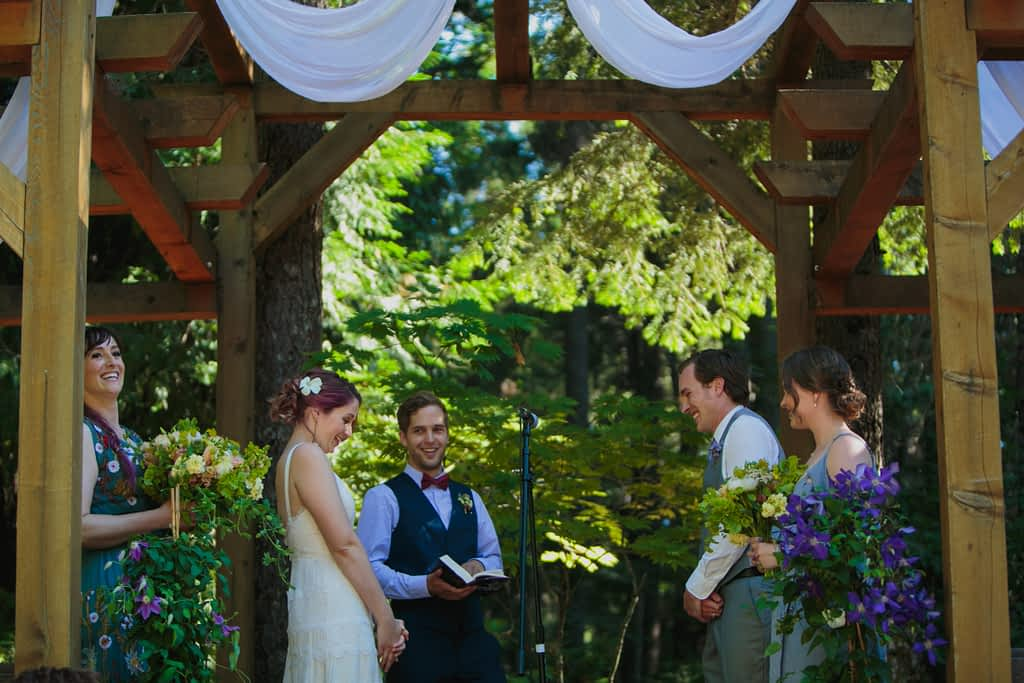 Bride and groom during their wedding ceremony under a white canopy and beautiful wood trellis.