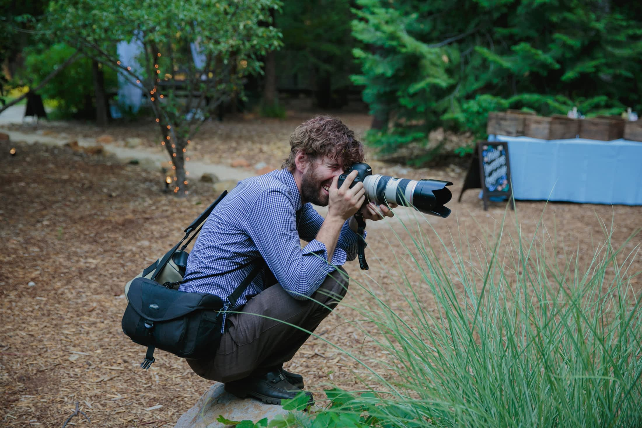 Maurice is crouching on rock while he shoots with his zoom lens, a 70-200mm.