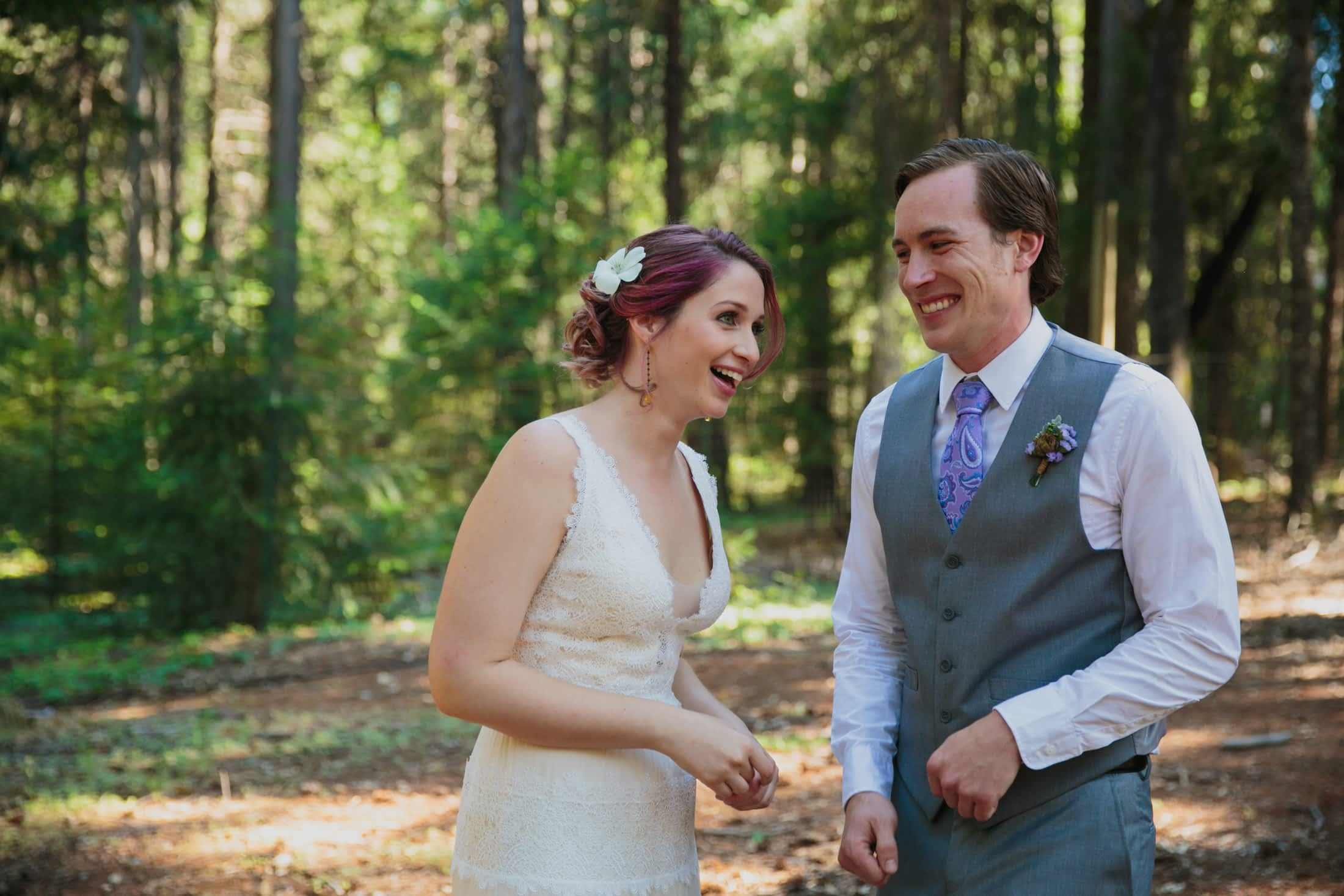 Bride and groom laughing in the woods.