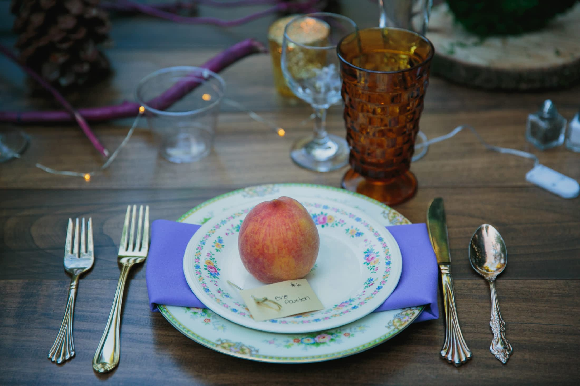 A single place-setting with a ripe peach on the vintage plate.