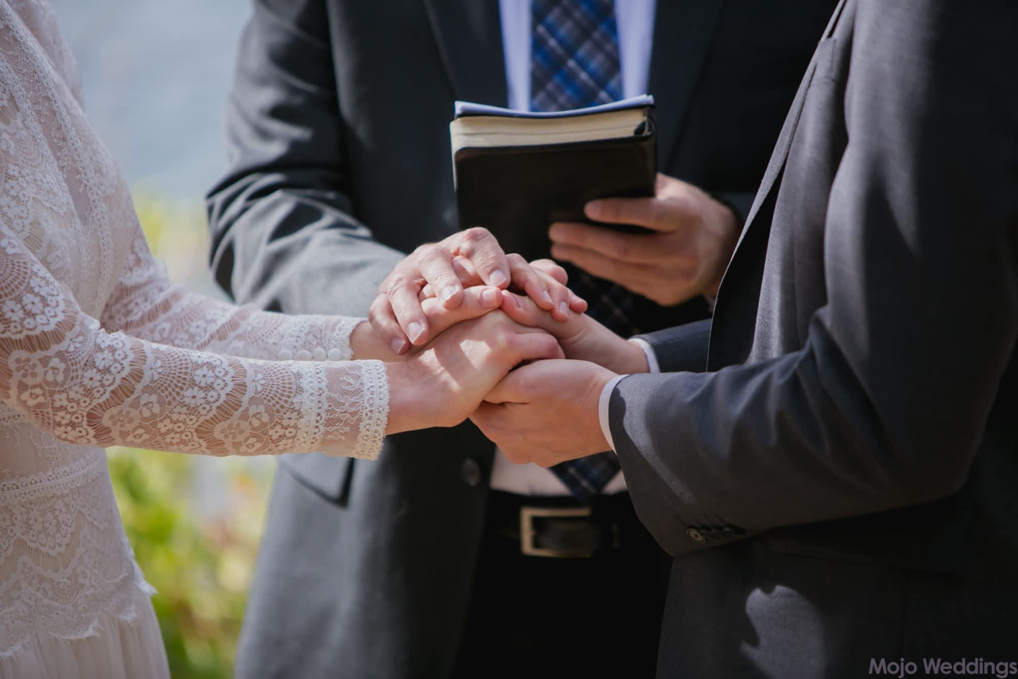 A close up of the hands of the bride, groom, and officiant.