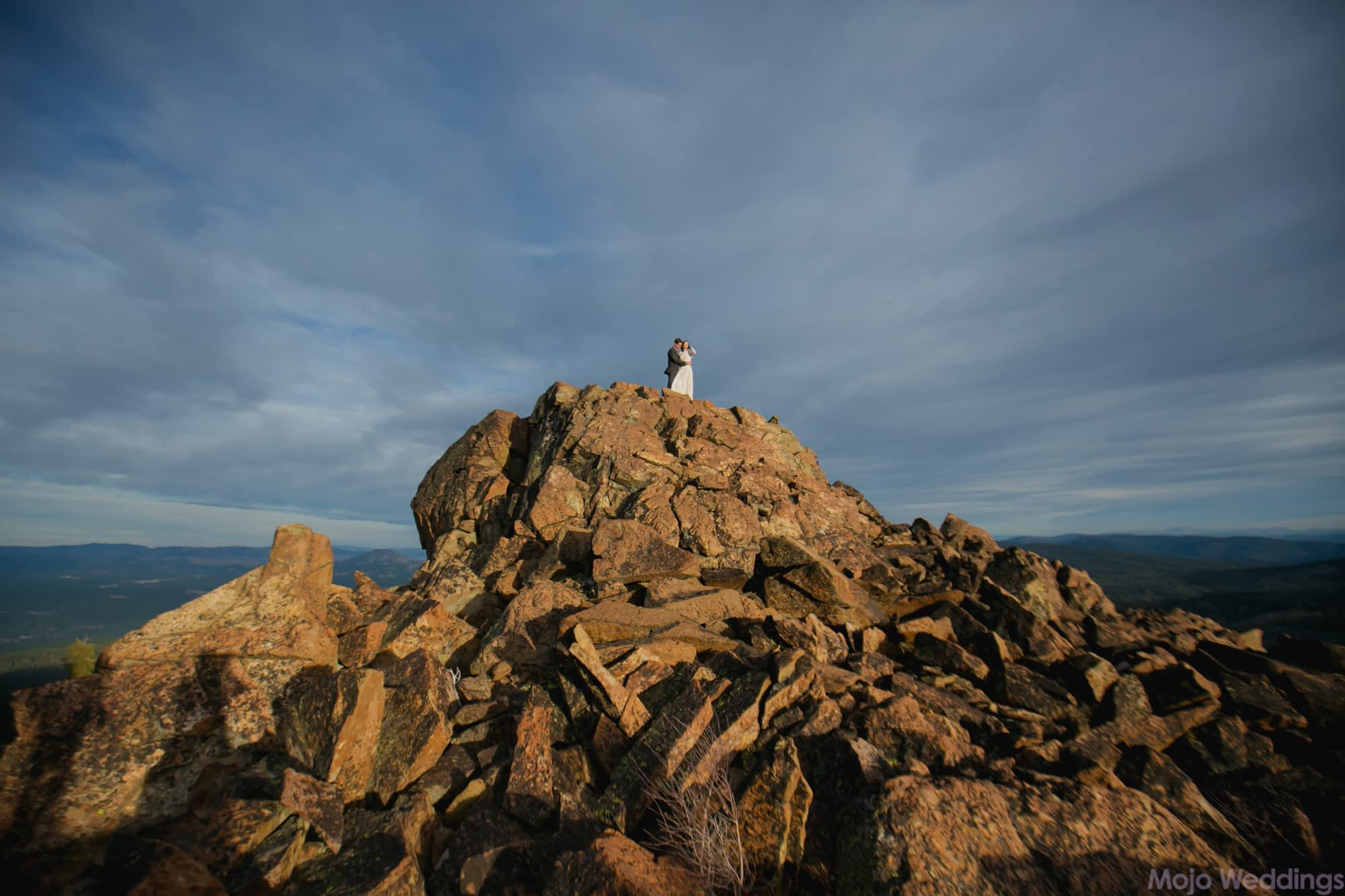 The bride and groom are small on top of a glowing orange rocky mountaintop with dark blue cloudy skies behind them.