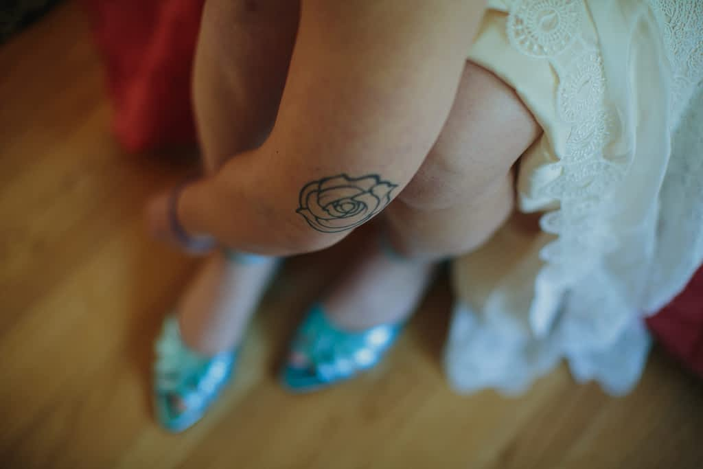 A rose tattoo is on the elbow of the bride as she buckles her blue wedding shoes.