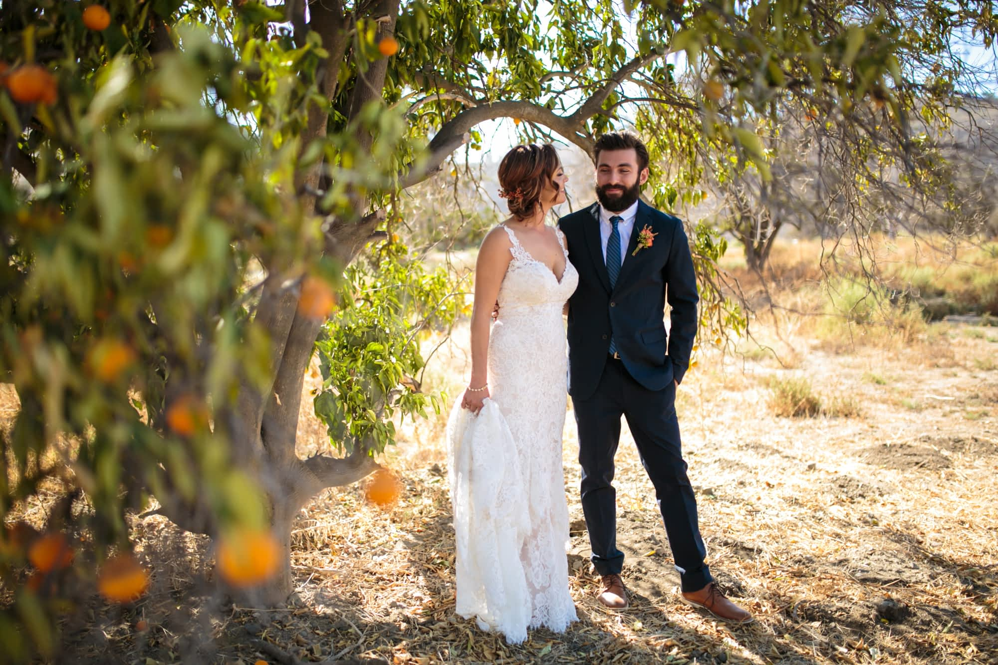 Couple stands under an orange tree.