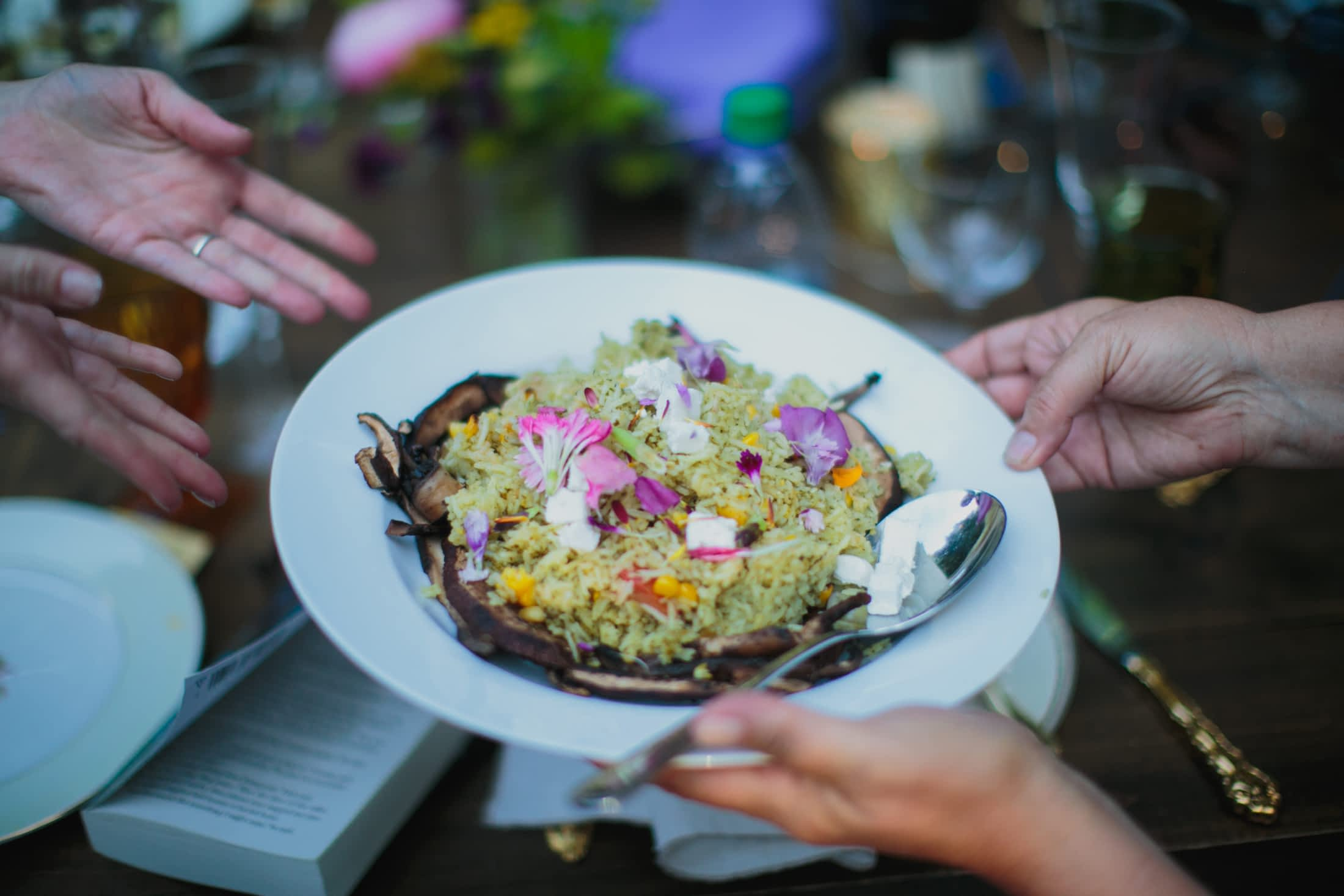 A plate of risotto and flower garnishes is being passed around at the family-style dinner.
