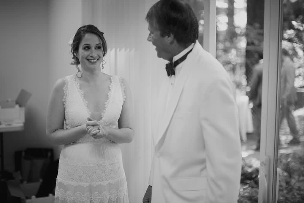 Bride and father-daughter smiling at each other as he enters the room and sees her for the first time.
