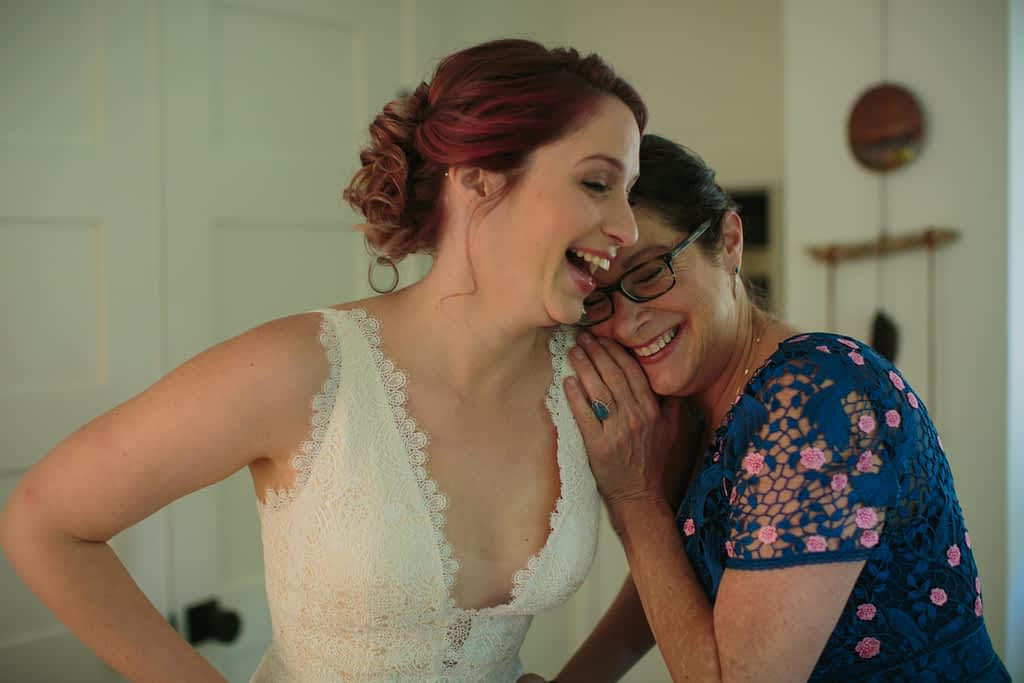 Bride laughing with her mother while getting ready for the wedding.