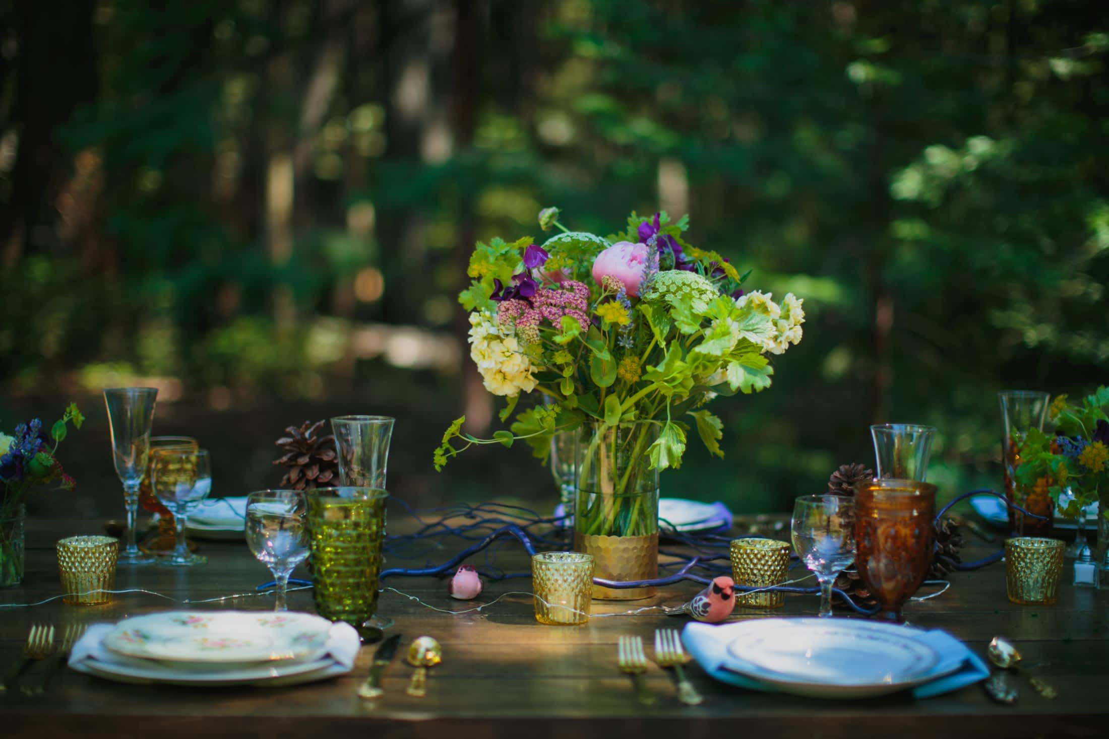 The table scape of flowers, mismatched glassware, vintage plates and pinecones.