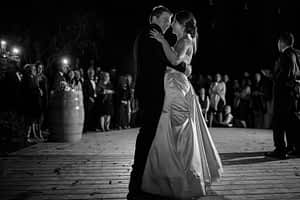 Black and white moody image of the bride and groom dancing with the dimly lit guests in the background.