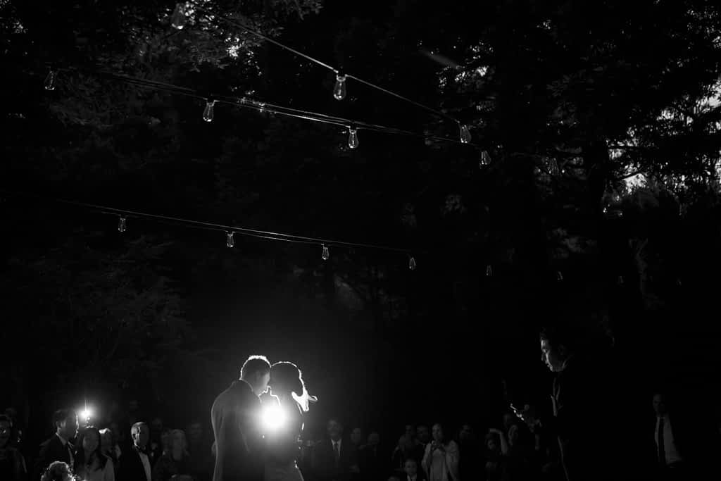 A light shines between the bride and groom and illuminates their silhouettes.