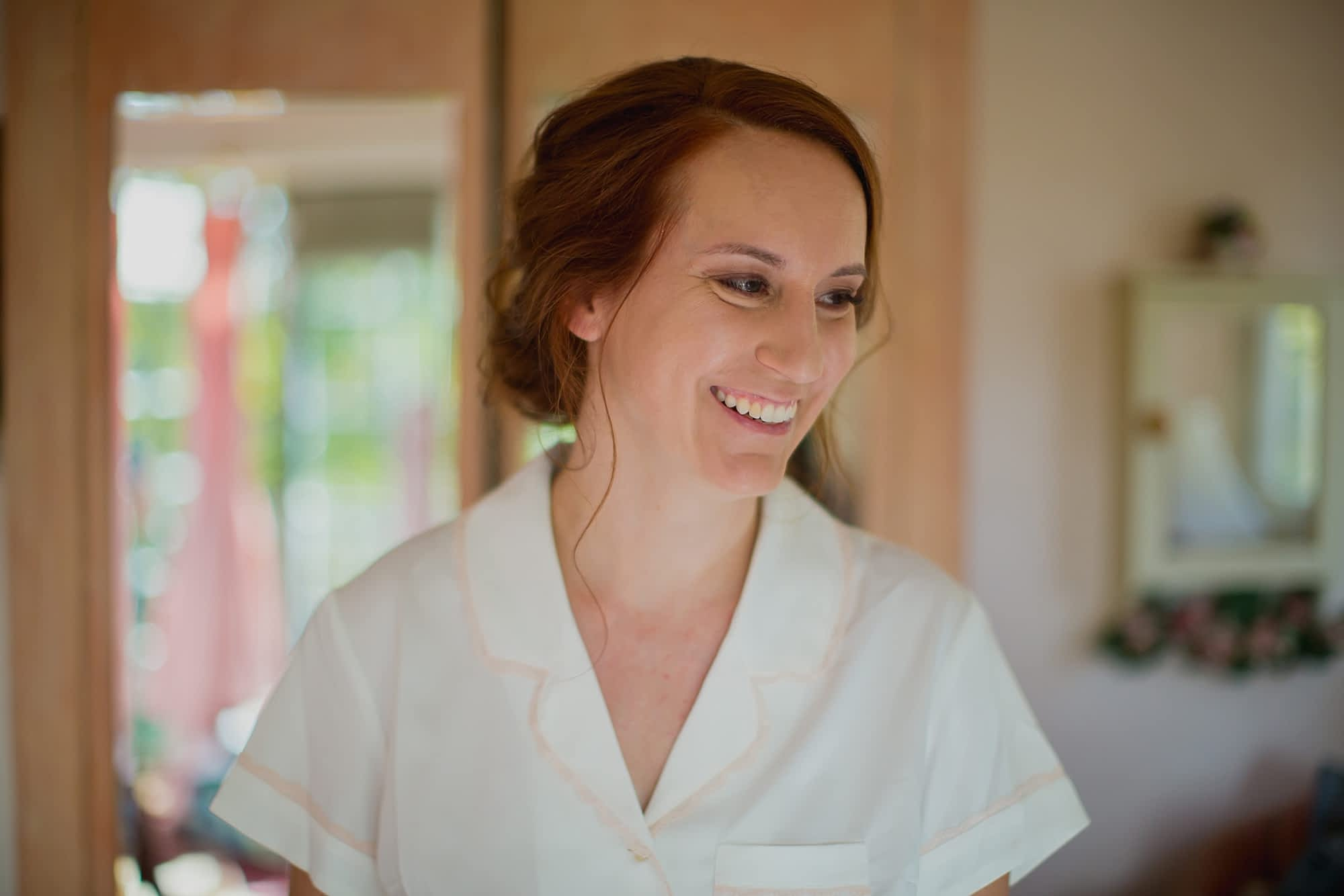 The bride smiles in her white button up shirt and her out of focus blush gown can be seen hanging in the doorway behind her.