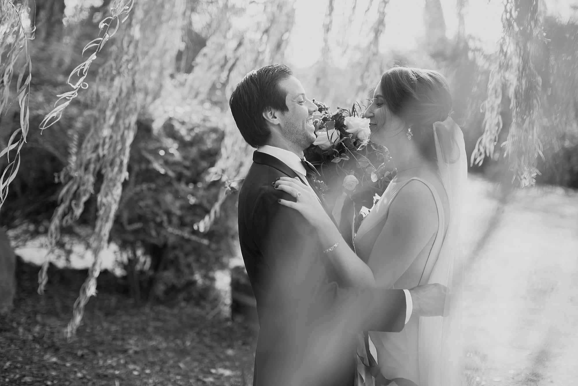 A black and white images of the bride and groom during their first look, surrounded by willow tree leaves.
