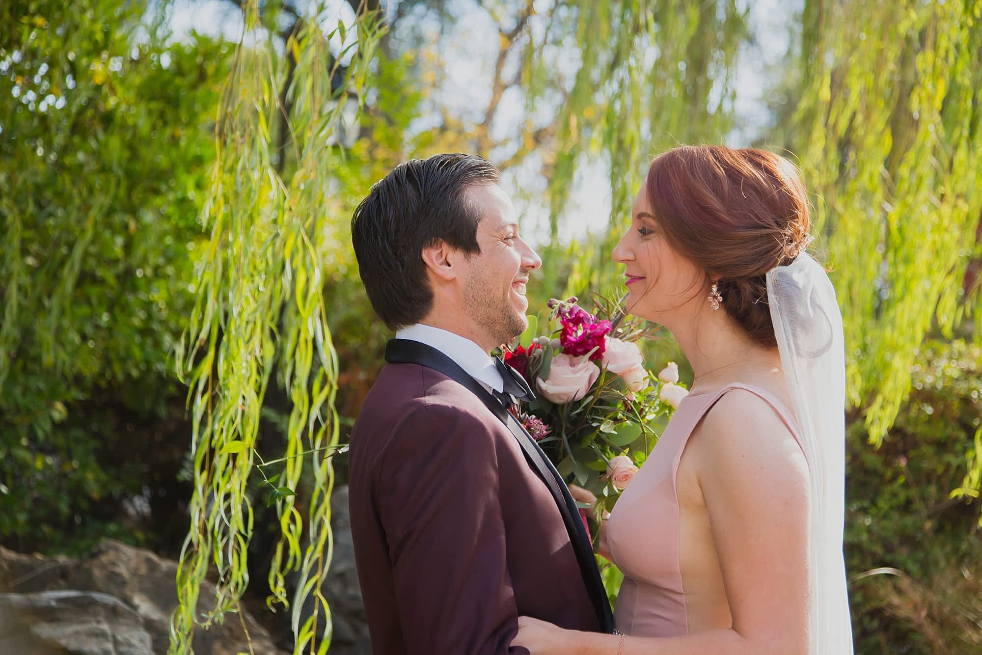 The bride and groom smile at each other while standing under a willow tree.