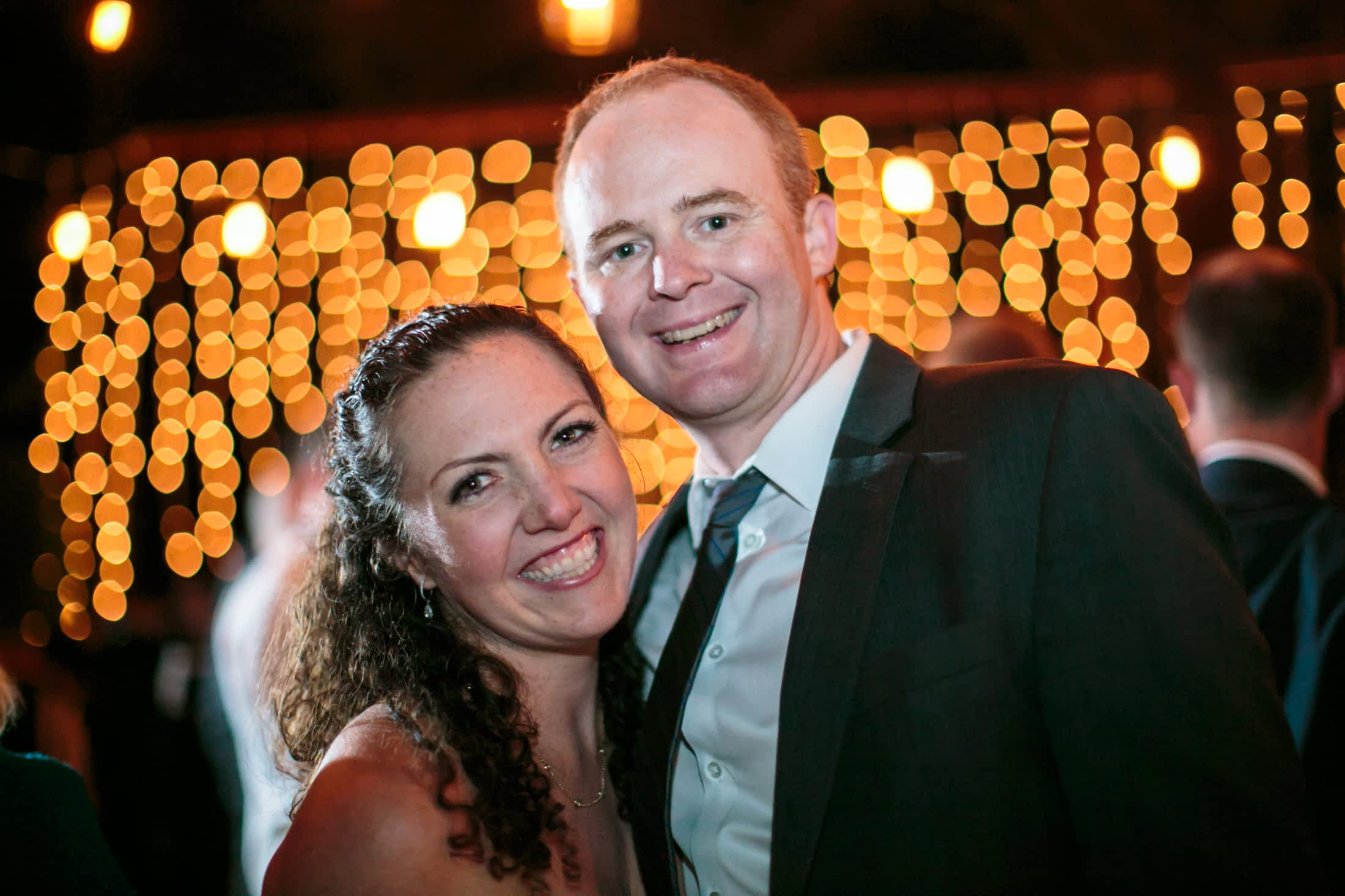 Smiling guests in front of a very sparkly, bokeh background.
