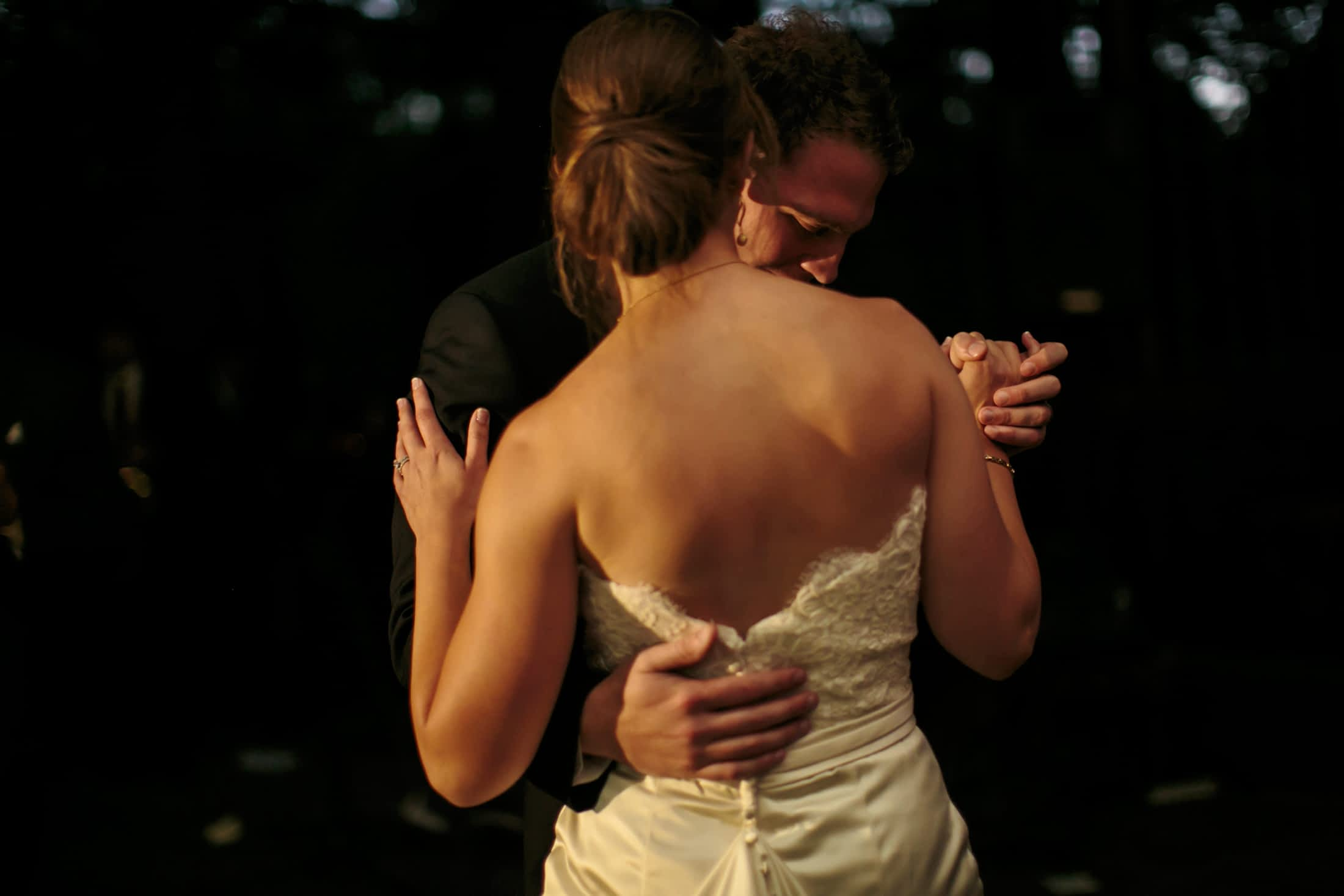 An up-close view from behind the bride as the groom holds her during their first dance.
