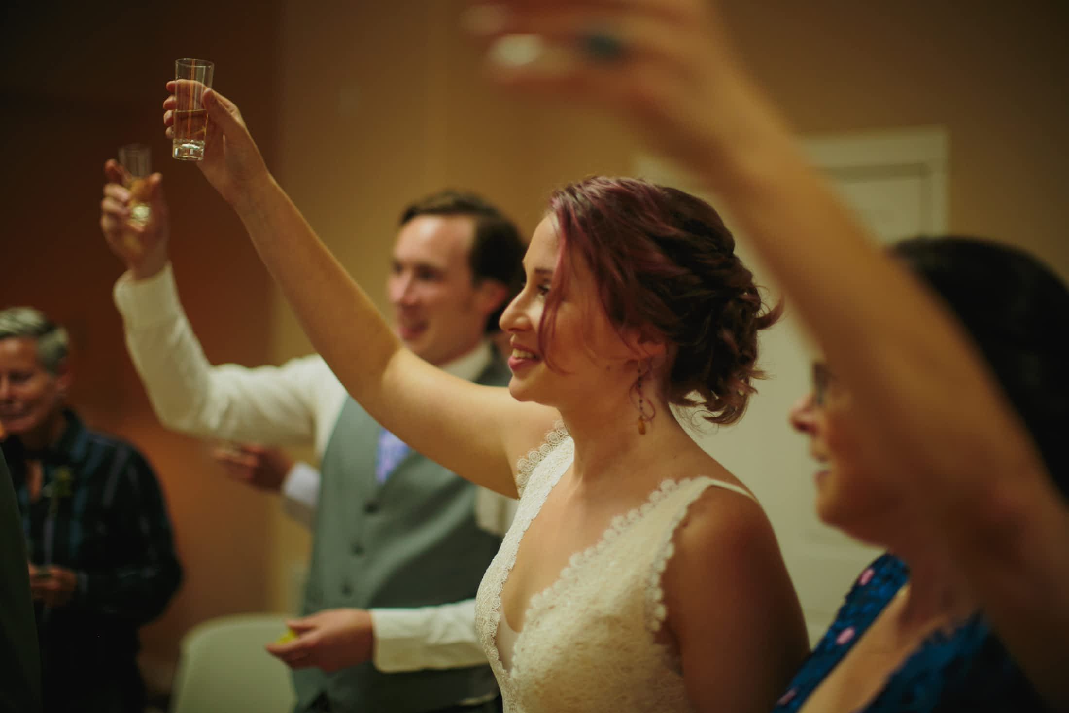 Bride and groom toasting with their family while doing a shot of tequila before their wedding ceremony.