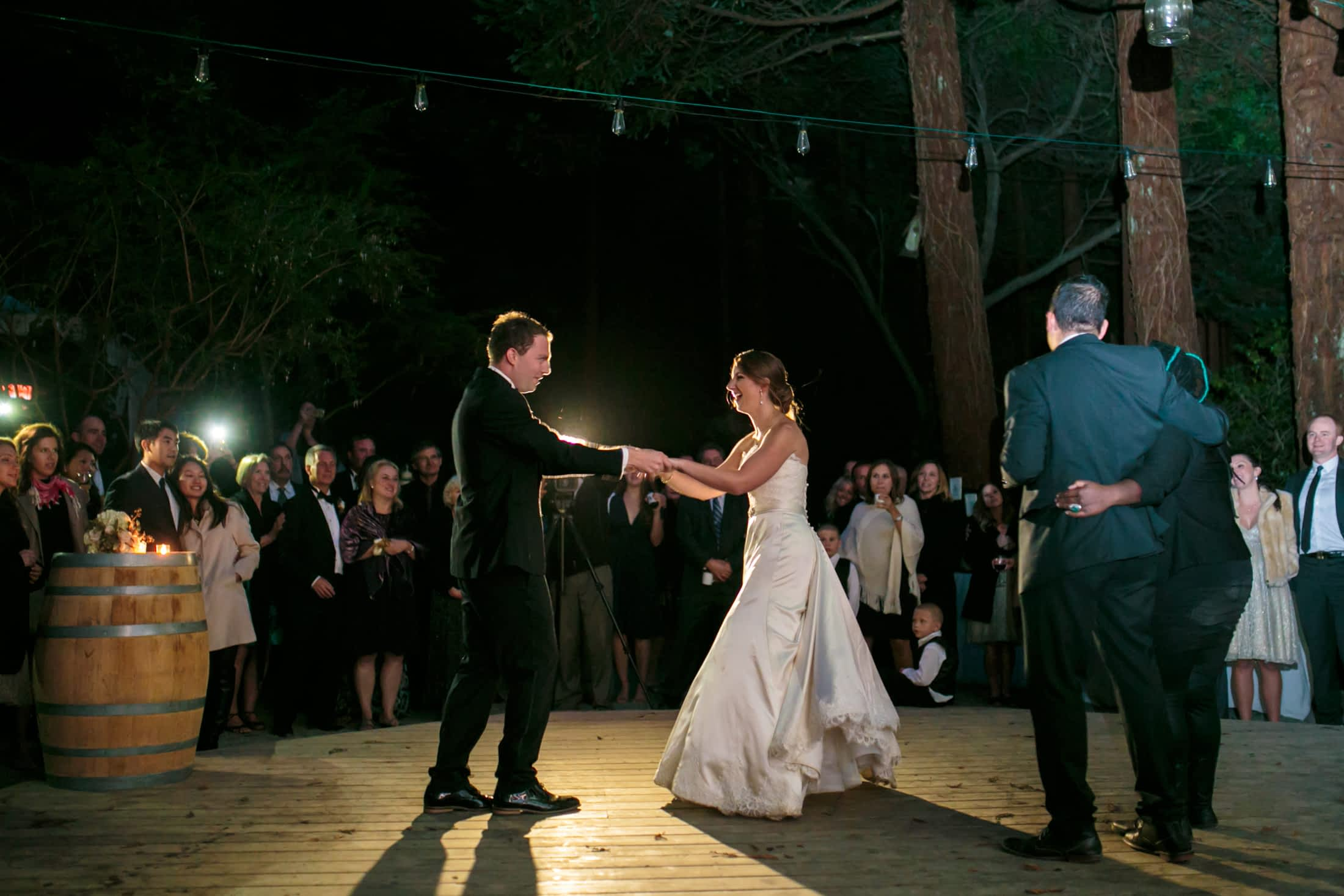 The bride and groom facing each other holding hands while dancing.