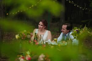 Abstract and out of focus greenery and pink flowers frame the bride and groom sitting and laughing at their sweetheart table.