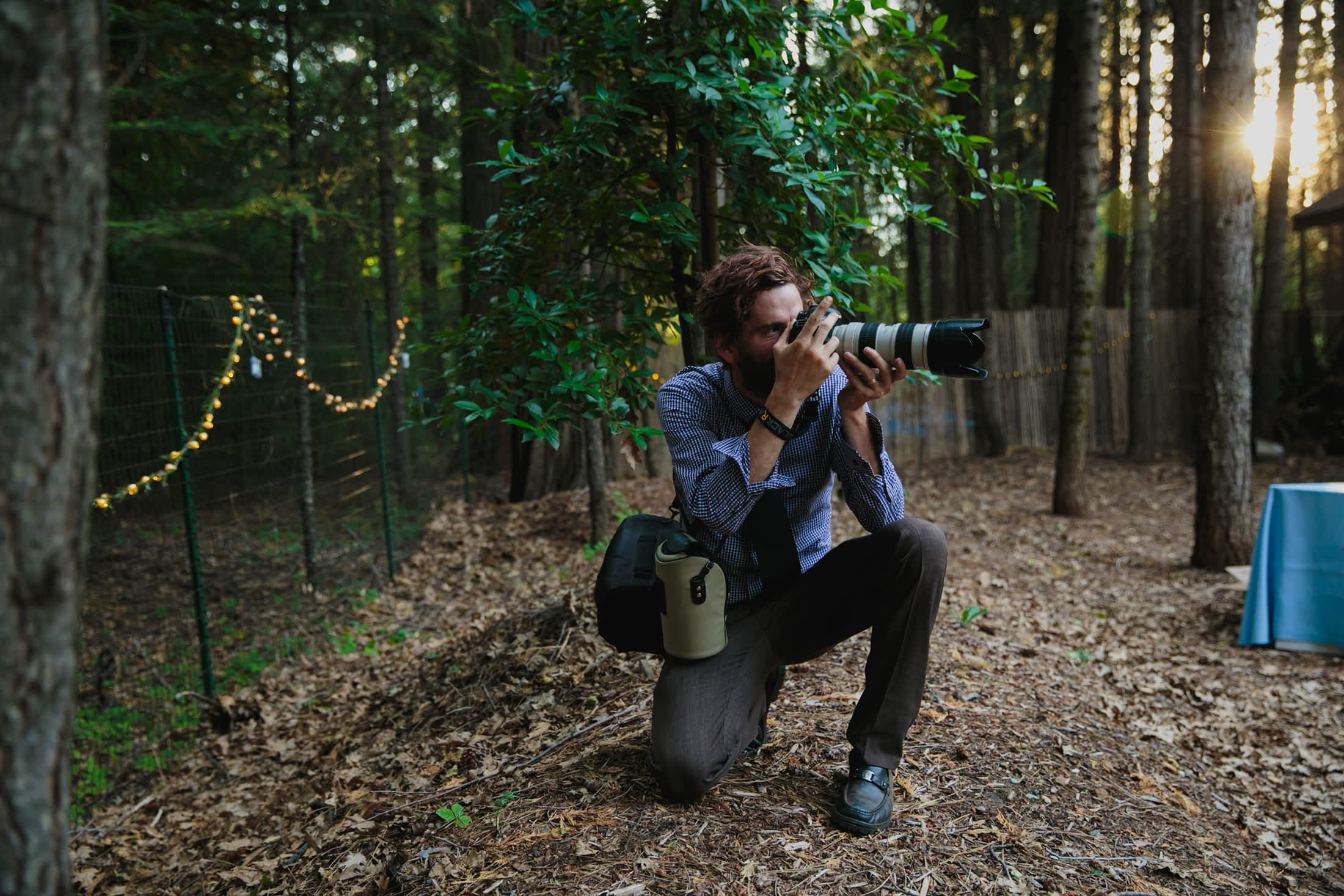Maurice kneels on one knee while photographing with the 70-200mm lens.
