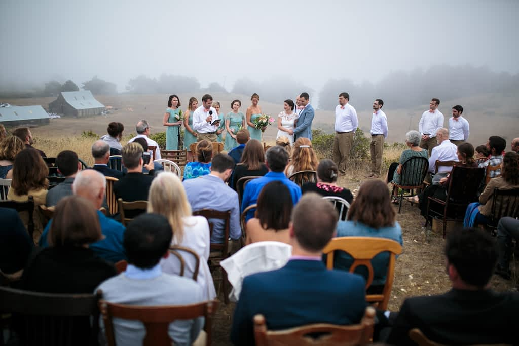 A foggy Mendocino hillside wedding with a barn in the distance.